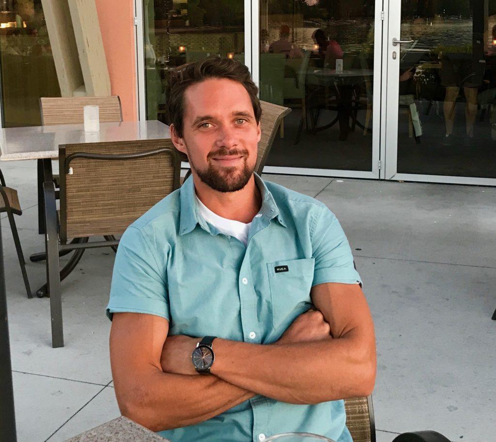 man sitting looking at camera and smiling